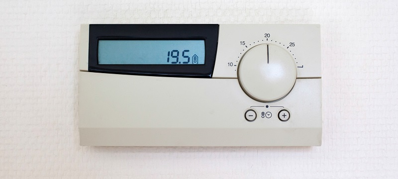 Digital Thermostat set to 19,5 degrees Celsius on white wall